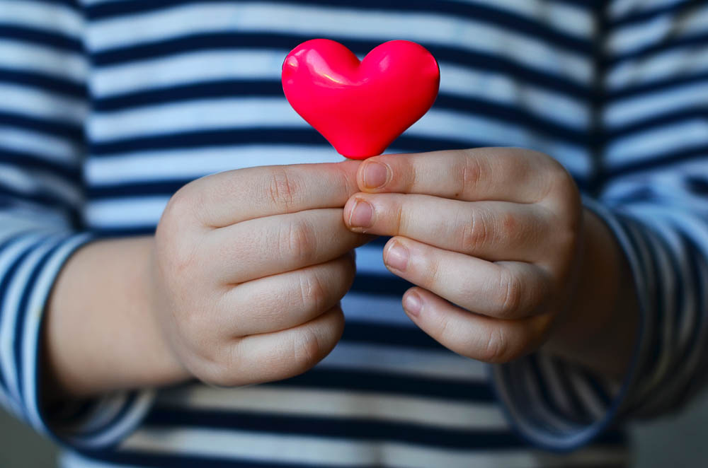 a small pink heart being held by a small child
